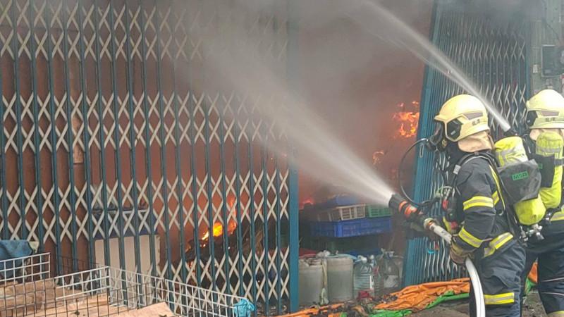 桃園市龍潭傳統市場擺貨倉庫冒火,消防隊封巷救火。(記者李容萍翻攝)