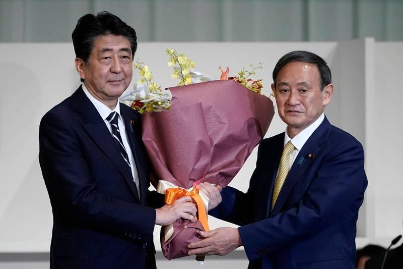 日本官房長官菅義偉(右)14日高票當選執政黨「自民黨」的新任總裁,安倍晉三(左)相當欣慰。(法新社)