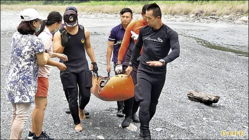 被水沖走的罹難者遺體由救難人員尋獲抬出,也令倖存的家屬心碎不已。(記者佟振國攝)