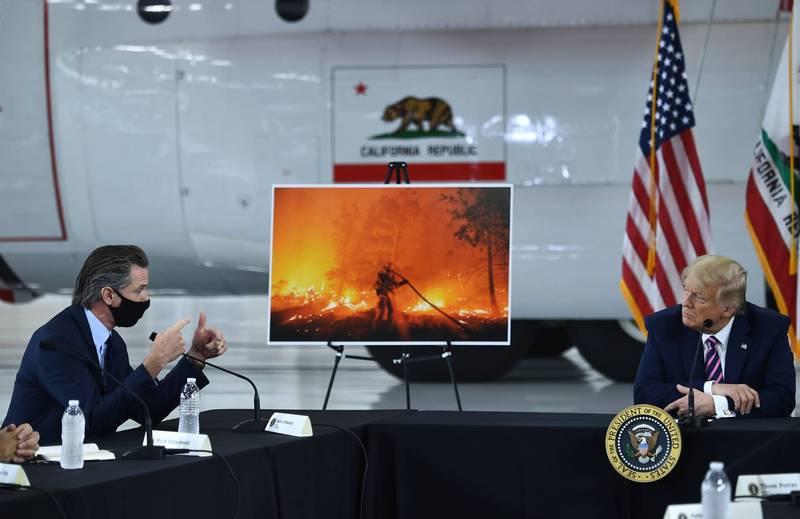 川普(右)14日到加州視察聽取野火災情簡報時,稱全球暖化將會逆轉並消除氣候變化,他說,「氣候會開始變涼啦」。左為加州州長紐森。(法新社)
