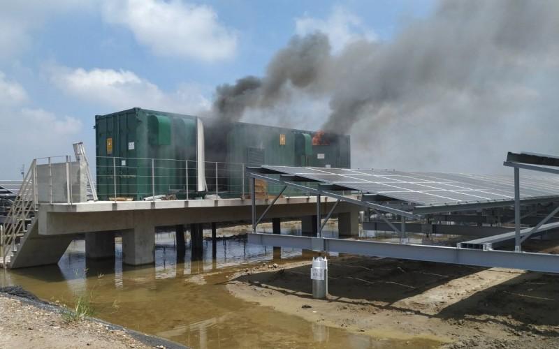 如貨櫃屋形狀的電流變流器控制設備起火冒煙。(記者楊金城翻攝)
