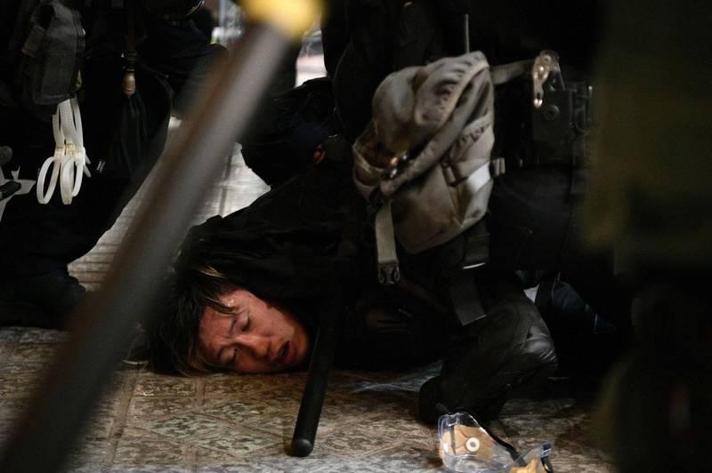 香港盧女、利男涉「襲警」罪嫌遭起訴,法官今裁定無罪。圖為香港示威者遭警方壓制,圖中人物與新聞事件無關。(法新社檔案照)