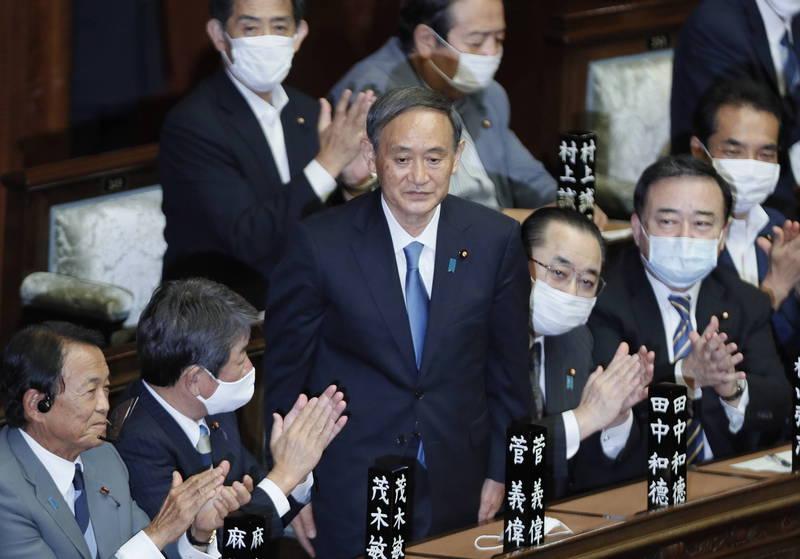 菅義偉(中)內閣今天上路,新的內閣共有20名閣員,麻生太郎(左)為副首相兼財務相。(歐新社)