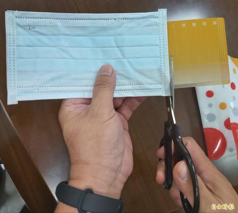 振興券塑膠卡套DIY變口罩夾方法,首先將口罩與塑膠卡套左邊對齊,用剪刀沿著虛線剪下卡套多餘部分。(記者張協昇攝)