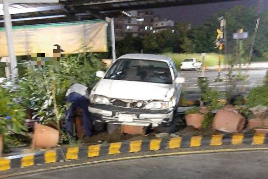白色的教練車將一排花盆撞翻,有個花盆還卡在底盤下。(圖擷自爆廢公社)