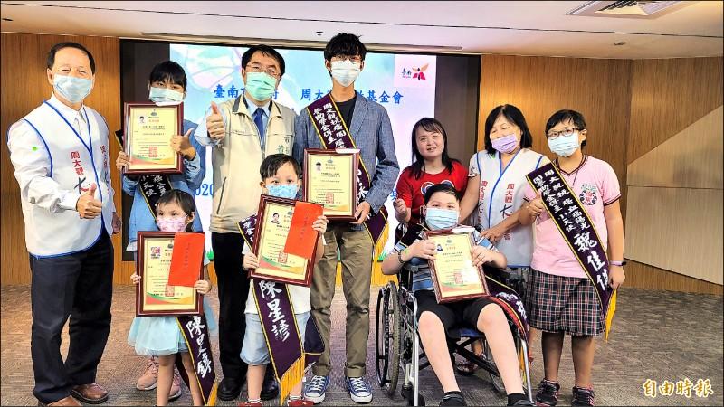 周大觀文教基金會創辦人周進華(左一)與台南市長黃偉哲(後排左三),頒發「抗癌圓夢基金」給南市獲獎的生命鬥士。(記者劉婉君攝)
