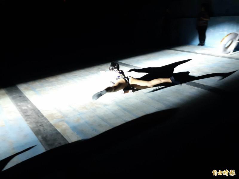 女舞者著泳裝在乾涸的縣立泳池乾泳。(記者黃明堂攝)