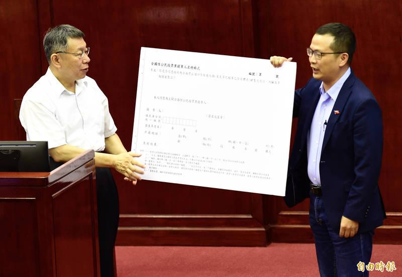 台北市議員羅智強(右)質詢時,拿出公投連署書手板給市長柯文哲(左)參考,柯文哲則說,再一段時間給民進黨準備、說明,「如果再不行,我就幫你簽」。(記者簡榮豐攝)