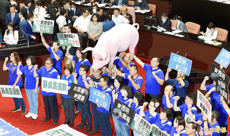 Chinese Nationalist Party (KMT) lawmakers yesterday hold placards and a pig mock-up on the floor of the Legislative Yuan in Taipei as they call on President Tsai Ing-wen to deliver a state of the union address, Premier Su Tseng-chang to apologize for the US pork imports policy and Council of Agriculture Minister Chen Chi-chung to step down, as Democratic Progressive Party lawmakers in the background guard Su and Minister of Health and Welfare Chen Shih-chung.  Photo: Liao Chen-huei, Taipei Times