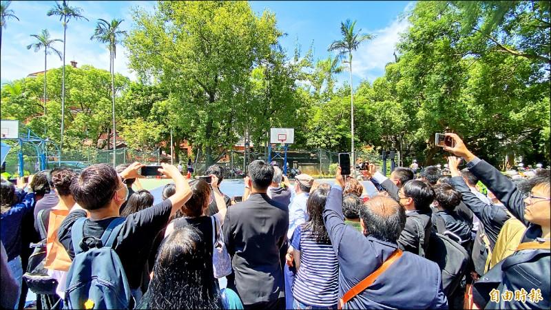 許多民眾報名參加在淡江中學舉行的前總統李登輝追思禮拜,在移靈車隊經過時,爭相拿起手機、相機拍攝。(記者黃欣柏攝)
