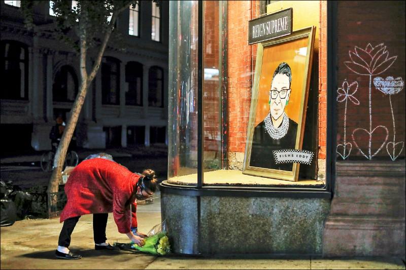 一名民眾十八日在紐約市百老匯一家商店所陳列的金斯伯格肖像前獻上悼念花束。(路透)