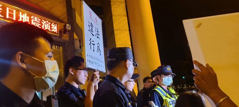 法稅改革聯盟動員支持者到新竹縣竹北警分局六家派出所前聲援被警方帶回調查的女志工時,遭警方舉牌警告違法集會。(現場民眾提供)