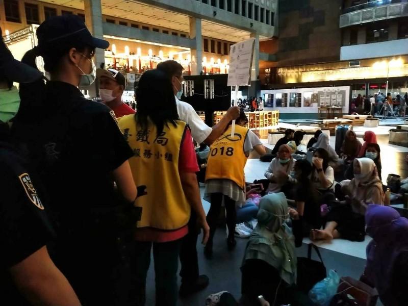 台北車站大廳今天出現多名外籍移工群聚用餐,台鐵現場與鐵路警察舉牌勸導。(台鐵提供)
