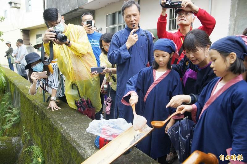 小朋友將字紙灰燼送入溪流,象徵漢字文化傳諸四方。(記者李容萍攝)