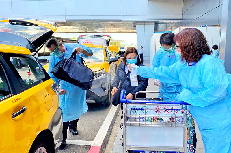 An airport staff member on Aug. 12 sprays disinfectant on a person leaving Taiwan Taoyuan International Airport as she prepares to take a taxi to where she is to be quarantined. Photo: CNA