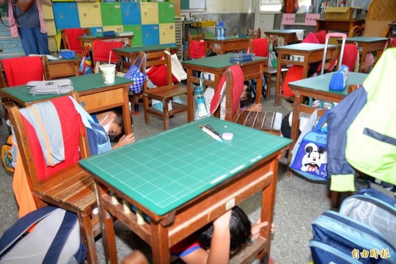 學生聽到地震警報後,迅速躲到桌底下。(記者詹士弘攝)