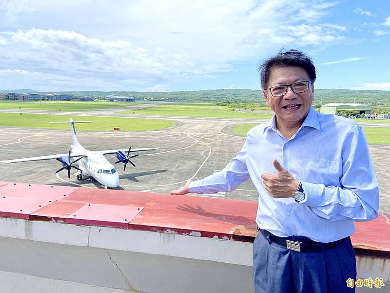 A charter flight from the Philippines is seen behind Pingtung County Commissioner Pan Men-an on the runway at Hengchun Airport yesterday.   Photo: Tsai Tsung-hsien, Taipei Times