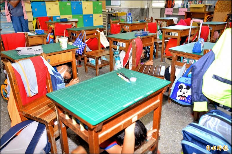 斗南石龜國小學童聽到地震警報後,迅速躲到桌底下。(記者詹士弘攝)