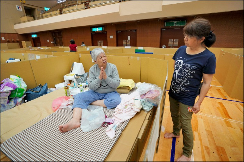 在日本九州熊本縣八代市一個臨時避難所裡,一名為躲避豪雨待在所內的68歲婦女(左)。圖中以紙板製成的隔間,是為了防止群聚造成武漢肺炎傳染。(歐新社檔案照)
