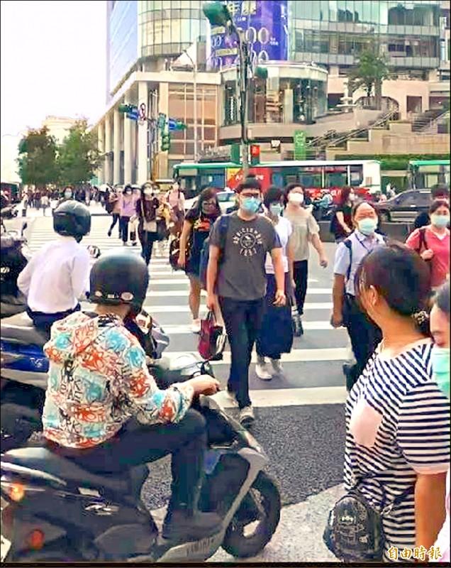 有些行人慢步穿越馬路,導致許多右轉汽機車嚴重回堵。(記者鄭名翔攝)
