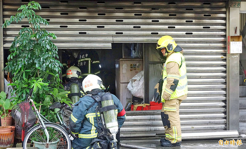 Firefighters look through the cut-open steel shutter of an unregistered long-term care facility in Taipei's Neihu District on Tuesday after putting out a fire that caused the death of three residents.  Photo: Chang Chia-ming, Taipei Times