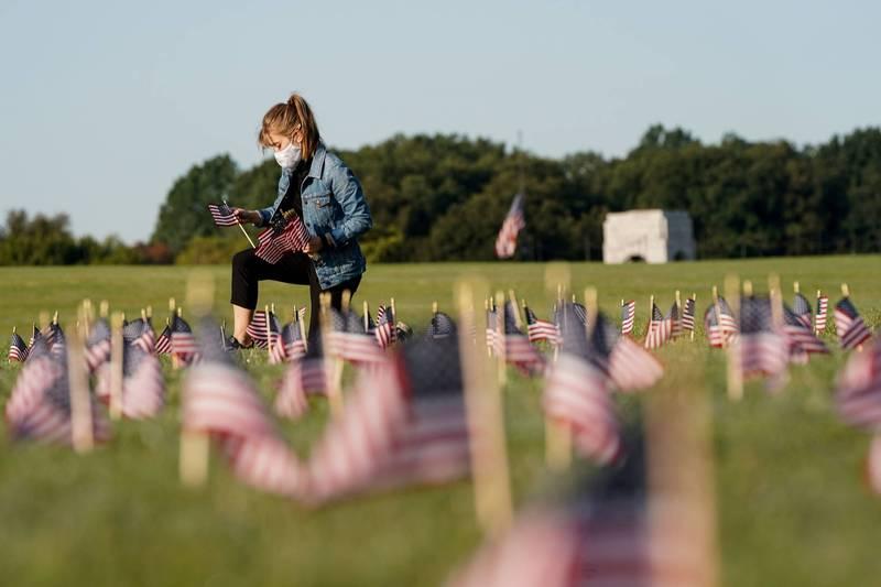圖為美國的志願民眾協助將國旗放置於華盛頓國家廣場上,以此紀念因武漢肺炎而喪生的20萬人。(路透)