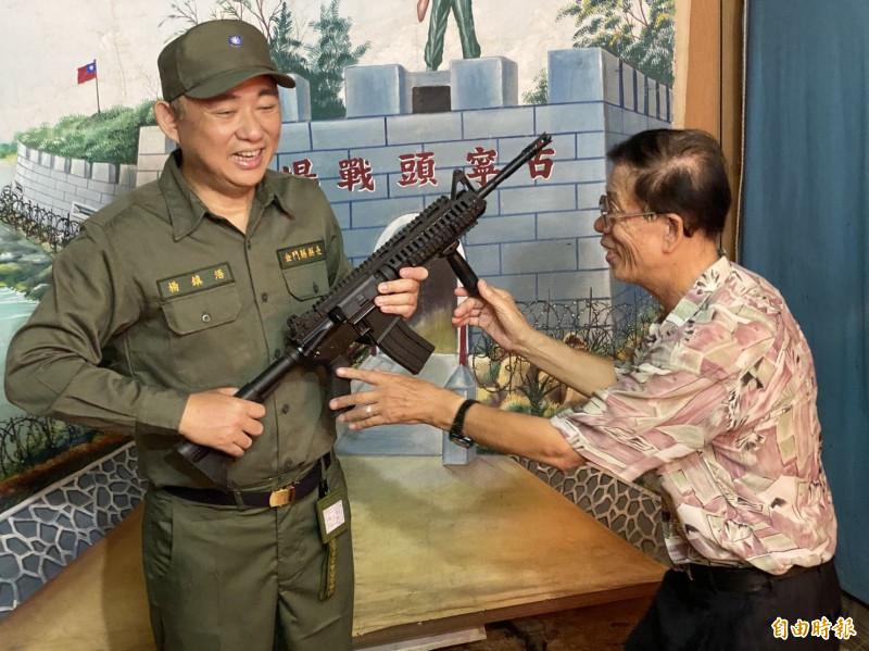 金龍相館老板李國明(右)指導縣長楊鎮浯(左)如何擺好拿槍姿勢。(記者吳正庭攝)