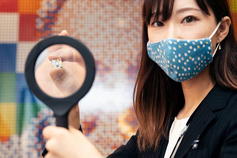 「日本發售40周年企畫展」在東京舉行,展覽方在記者會上秀出目前全球最小的魔術方塊。(美聯社)