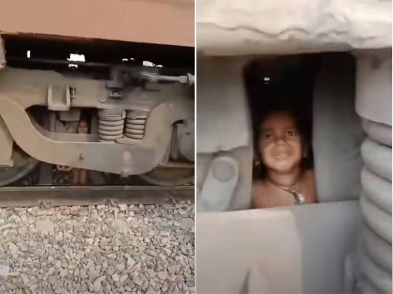 印度日前一處車站驚傳男童落軌遭火車輾過,沒想到男童奇蹟似的毫髮無傷,只是被卡在火車引擎下,當下神情慌張。(圖擷取自YouTube)