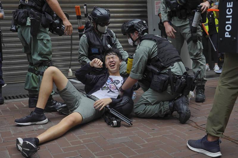 香港警方宣布修改《警察通例》中的「傳播媒體代表」定義,限縮傳媒代表資格,變相封殺學生和公民記者、網路自媒體。對此,包含香港記者協會等多個傳媒工會今日舉行記者會,要求港警取消修改定義,否則不排除採取法律行動。圖為港警向1名記者噴灑胡椒水。(美聯社)