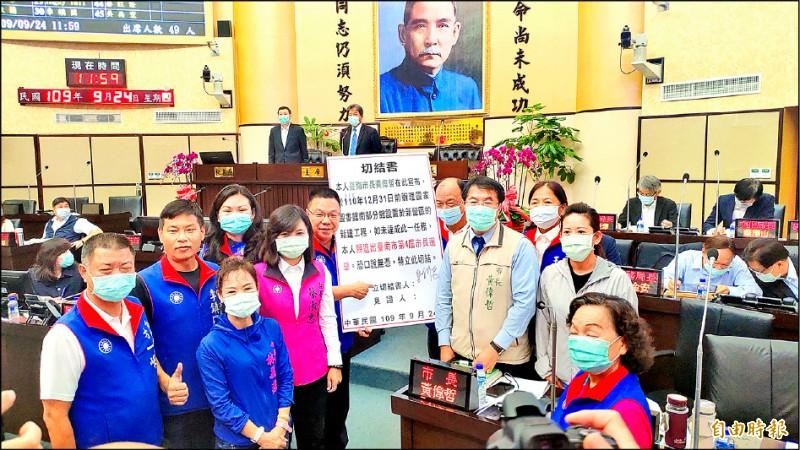 國民黨議員一時不察,拿著看板開心與黃偉哲合影。(記者蔡文居攝)
