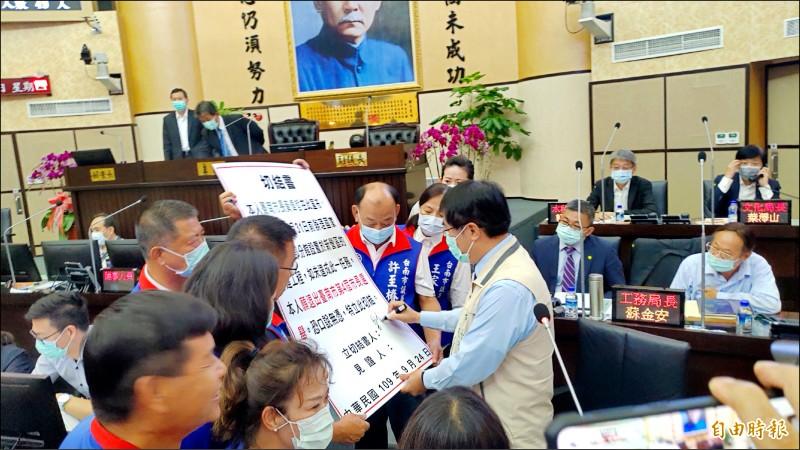 在議員的要求下,黃偉哲在國圖工程切結書看板上簽名切結。(記者蔡文居攝)