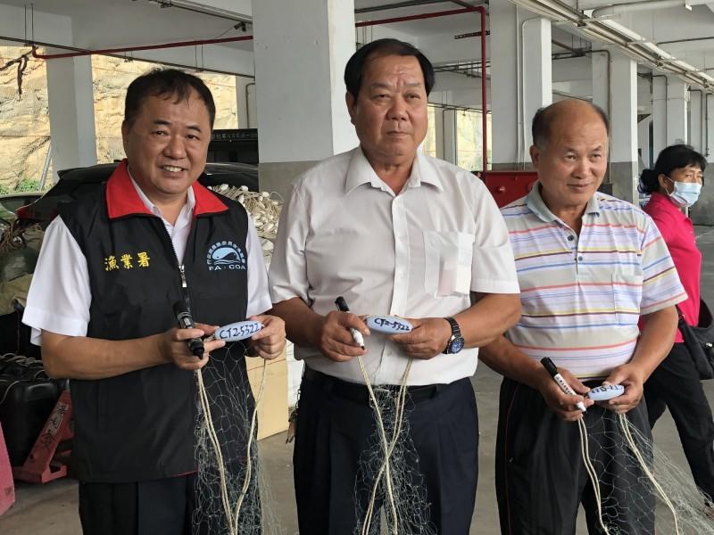 農委會漁業署長張致盛(左)、金門區漁會理事長吳安樂(中)等人,在金門新湖漁港示範標示漁船編號。(金門區漁會提供)