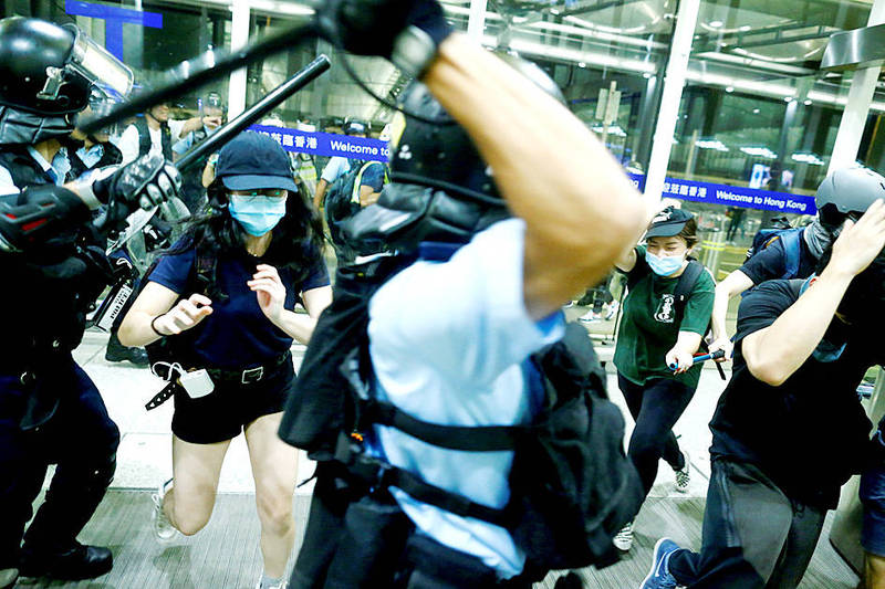 Riot police disperse anti-government protesters at Hong Kong International Airport on Aug. 13 last year. Photo: Reuters