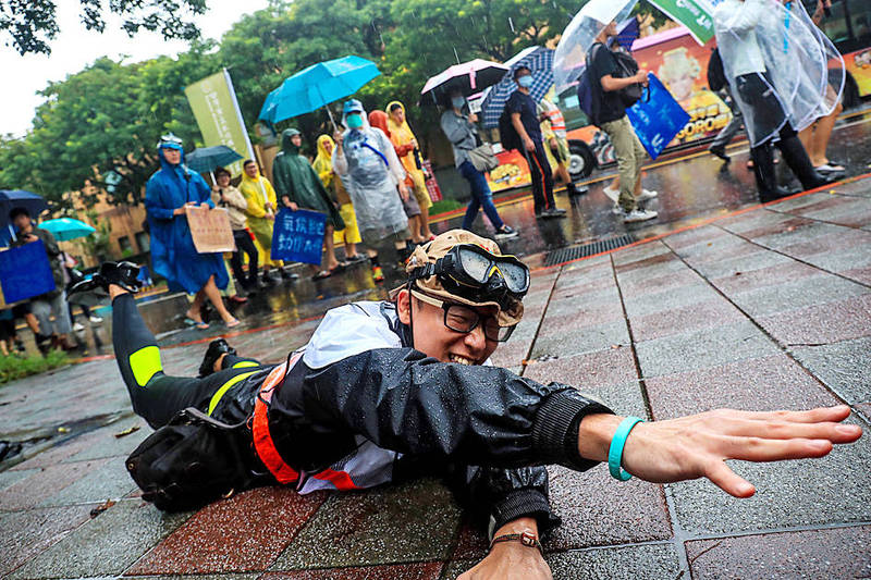 A participant in a march in Taipei yesterday pretends to swim through a flood caused by rising sea levels brought about by global warming. Photo: CNA