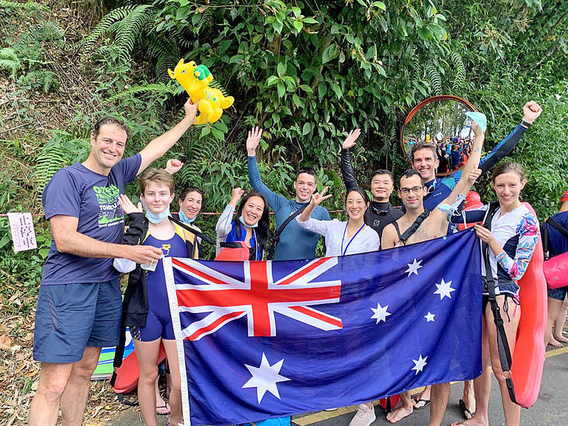 Australian Representative to Taiwan Gary Cowan, left, Australian Office in Taipei staff and other people hold an Australian flag at the annual Sun Moon Lake International Swimming Carnival in Nantou County yesterday. Photo courtesy of the Australian Office in Taipei