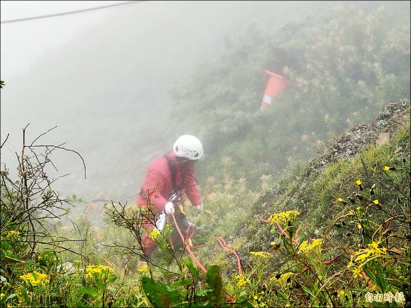 救難人員以繩索等裝備,垂降至合歡山武嶺停車場周邊山谷清除垃圾,一旁就有被風吹落的道路三角錐。(記者佟振國攝)