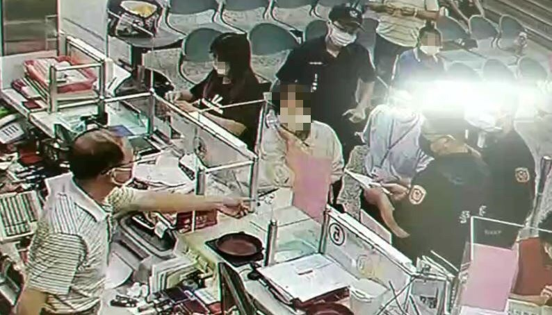 保七員警與行員在櫃檯前勸阻阿嬤匯款。(記者許國楨翻攝)