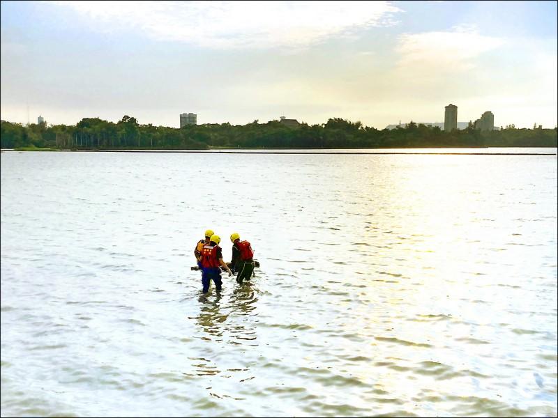 高雄市澄清湖昨驚見一對男女浮屍,兩人各揹著裝有大石頭背包,並用紅繩綁住彼此;圖為消防人員進行打撈。(記者洪臣宏翻攝)