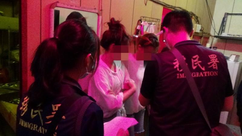 移民署幹員仔細盤查涉嫌賣淫外籍女子。(記者林國賢翻攝)