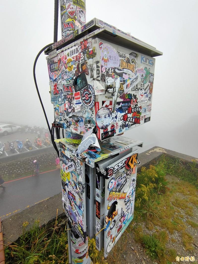 合歡山武嶺亭監視器桿及電箱被貼滿各式貼紙。(記者佟振國攝)