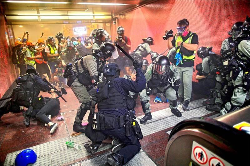 香港警方在港鐵內暴打示威者畫面。(美聯社)