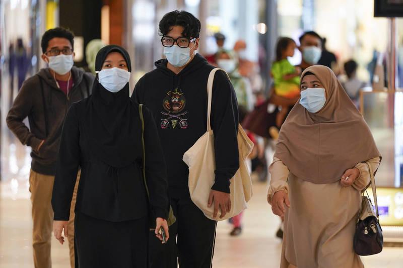 圖為1日馬來西亞購物商場,逛街民眾戴上口罩防武肺。(美聯社)