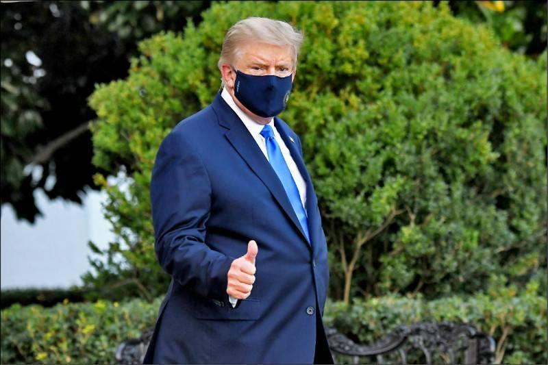 美國總統川普在美東時間2日傍晚,從白宮搭乘陸戰隊一號直升機前往華府近郊的軍醫院治療與隔離,他戴上口罩並向在場守候的媒體比讚,似乎是藉此為自己打氣並宣示會努力戰勝病魔。(法新社)