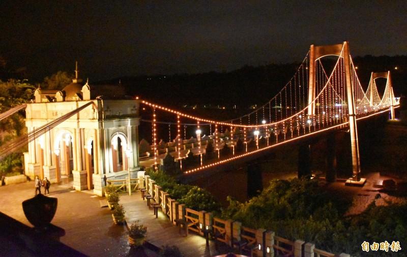 入夜後的大溪觀光吊橋,在LED燈照射下,成為情侶約會、放閃的最佳景點。(記者李容萍攝)