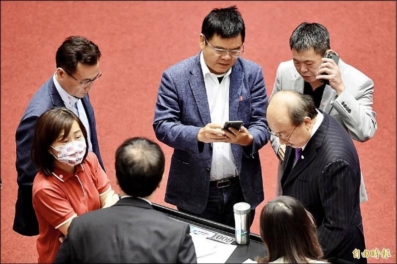 立法院院會昨日無異議通過「台美復交」、促美軍協防台灣兩項公決案。圖為民進黨、國民黨立委在議場內交換意見。(記者叢昌瑾攝)