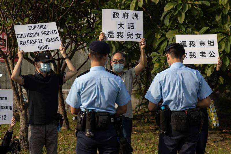 香港飛行服務隊被踢爆,疑似配合中國警方將12名港人「送中」。圖為12名港人親友在飛行服務隊外舉標語抗議。(歐新社)