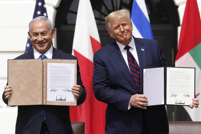 在美國總統川普(右)主持下,以色列總理納坦雅胡(左)上月15日與巴林以及阿拉伯聯合大公國簽訂了關係正常化協議。(彭博)