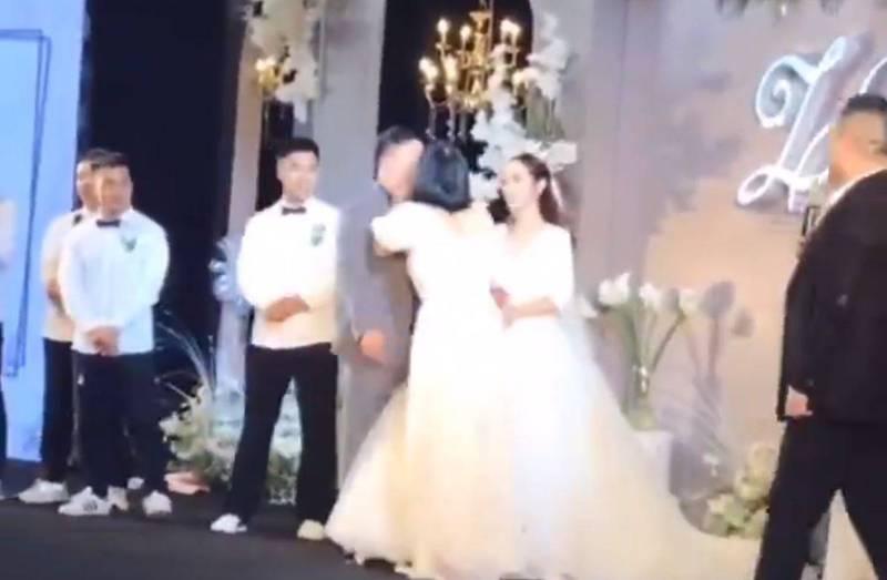 中國河南一對新人在親友的見證下結為連理,沒想到一旁的伴娘突然提起裙子奔向新郎,還當眾激吻新郎,讓全場氣氛凝結。(圖擷取自微博)