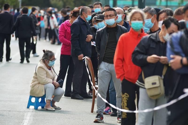 青島近日爆發本土武漢肺炎疫情。圖為青島市民排隊等候接受採檢。(法新社)